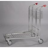 Plošinový nákupní vozík s červeným madlem.